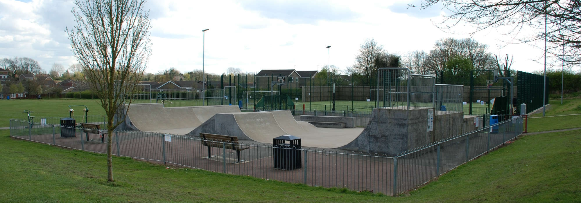 Activity Park. a gated skatepark, with various skating apparatus and a bench