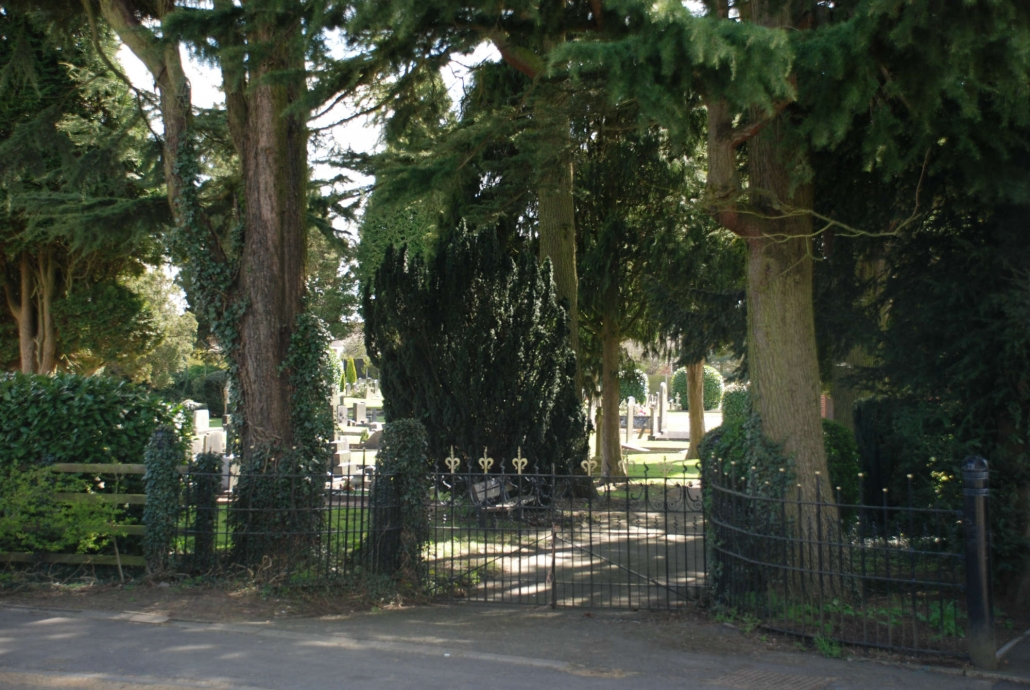 Small cemetery gates, trees surrounding the gates, multiple burial stones can be seen in the far background